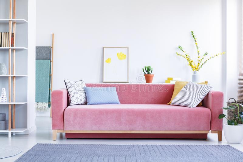 Kolorowe poduszki na dużej, aksamitnej, różowej kanapie w zabawie, przestronnej obraz royalty free