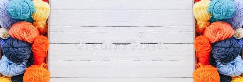 Kolorowe przędz piłki w drewnianym pudełku na białym drewnie wsiadają tło zdjęcia royalty free