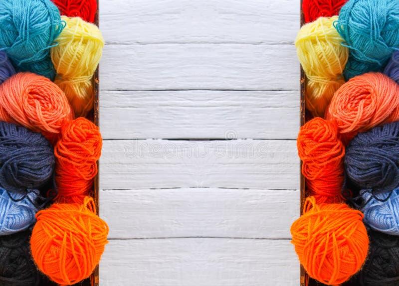 Kolorowe przędz piłki w drewnianym pudełku na białym drewnie wsiadają tło fotografia royalty free
