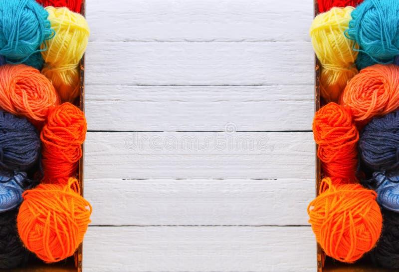 Kolorowe przędz piłki w pudełku na białym drewnie wsiadają tło obraz stock
