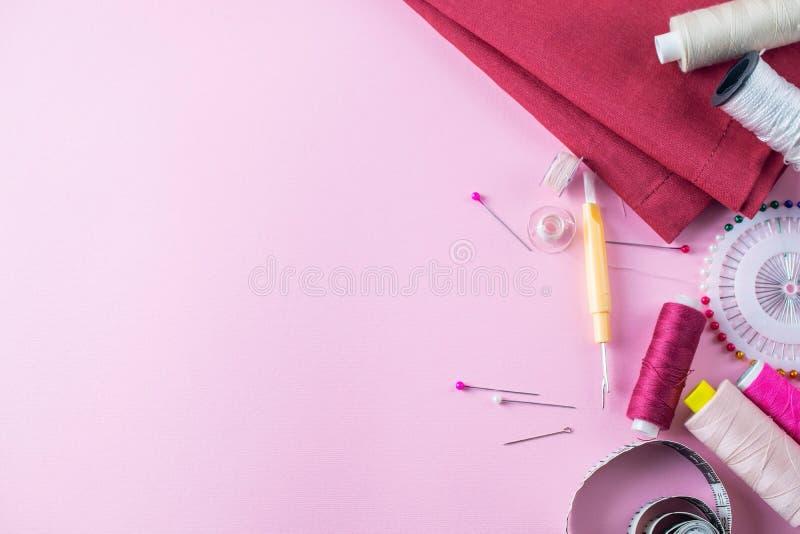 Kolorowe szwalne nici na r??owym tle, mieszkanie nieatutowy obrazy stock