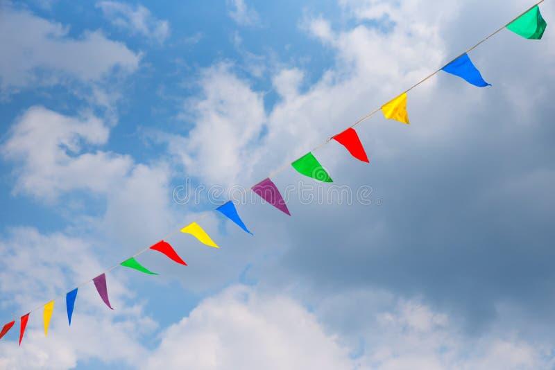 Kolorowe trójgraniaste flagi na linii przeciw chmurnemu niebu, pionowo zdjęcie stock
