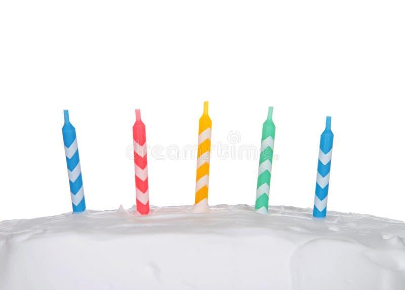 Kolorowe urodzinowe świeczki na biel oszroniejącym torcie zamykają w górę fotografia royalty free