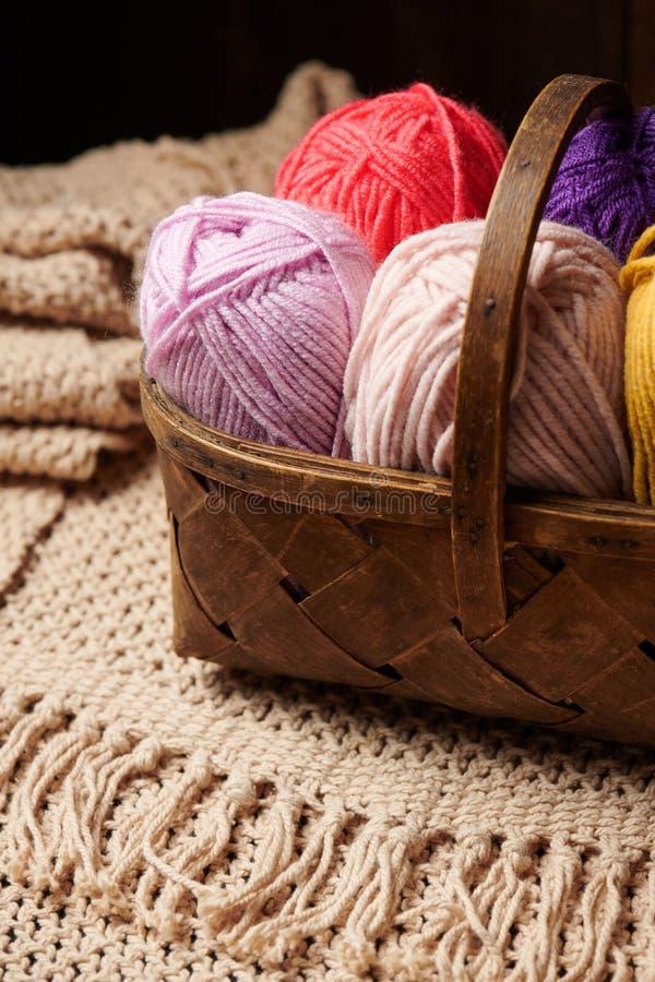 Kolorowe wełien nici dla dziać w koszu, drewniany tło zdjęcie stock