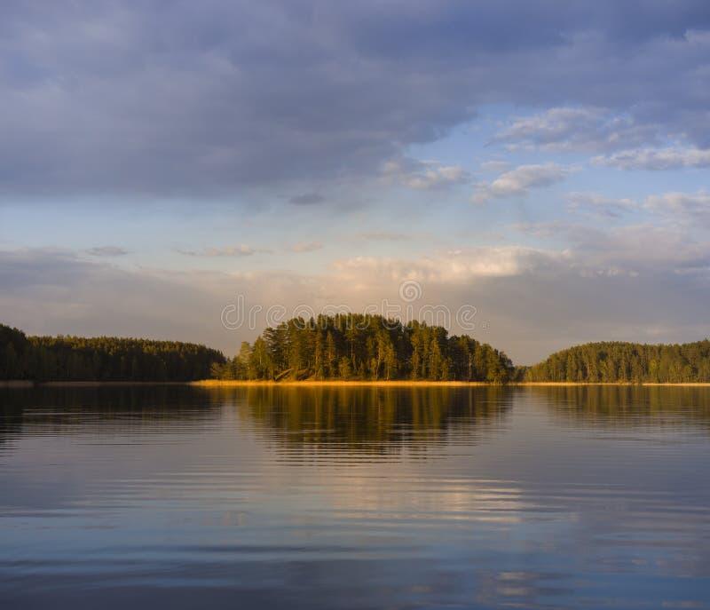 Kolorowe wieczorne promienie słoneczne padające na małą wyspę w jeziorze w ciepły letni wieczór fotografia royalty free