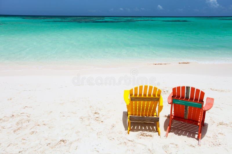 Kolorowi adirondack holu krzesła przy Karaiby plażą fotografia royalty free