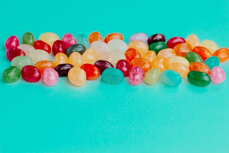 Kolorowi bobowi słodcy cukierki na turkusowego błękita tle 2 forsują pisklęca pojęcia Easter jajek kwiatów trawa malujących umies zdjęcia royalty free