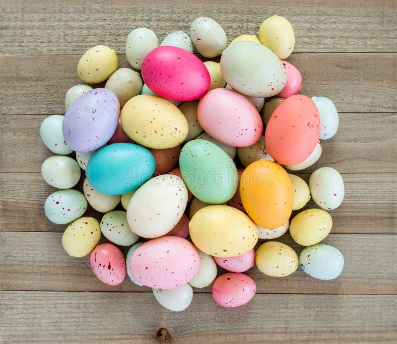 Kolorowi cętkowani Wielkanocni jajka wypiętrzali w górę drewnianego tła dalej fotografia stock