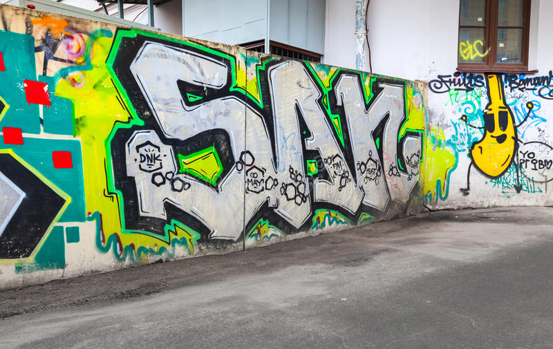 Kolorowi chaotyczni graffiti malujący nad starym ogrodzeniem zdjęcia stock