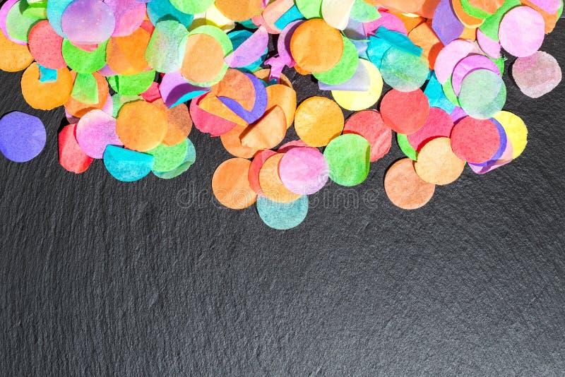 Kolorowi confetti na czarnym iłołupku jako szablon dla świętowania zdjęcie stock