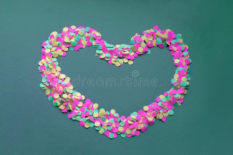 Kolorowi confetti w formie serca na ciemnym tle fotografia stock