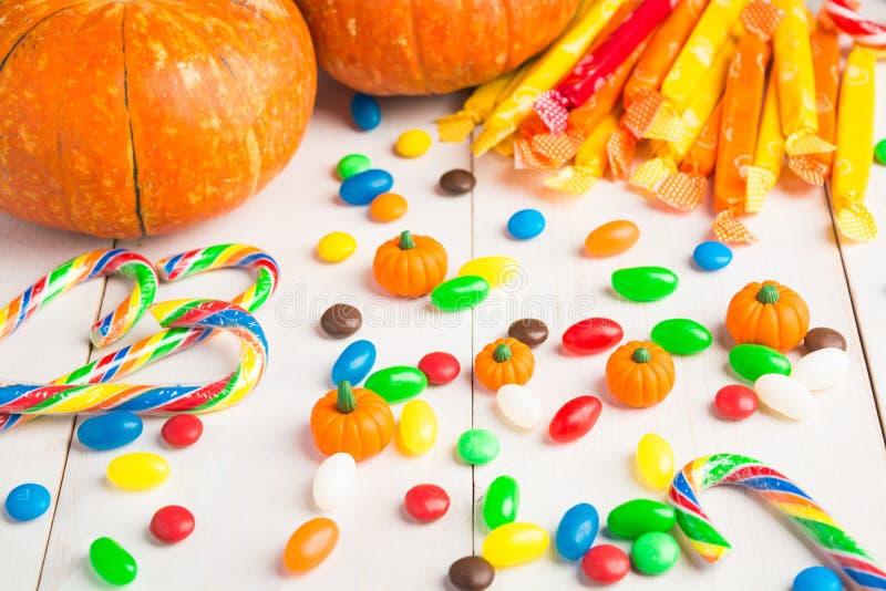 Kolorowi cukierki z banią nad białym drewnianym tłem obraz royalty free