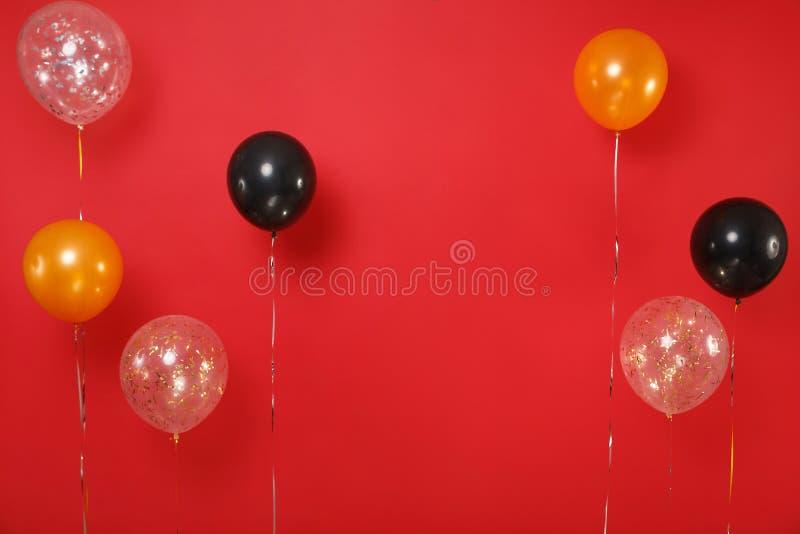 Kolorowi czarni złoci helowi lotniczy balony na jaskrawym zmroku - czerwony tło Dekoracja dla urodzinowego wakacyjnego nowego rok fotografia royalty free