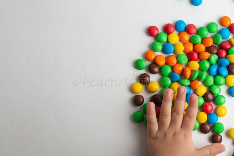 Kolorowi czekoladowi cukierki na białym tle z dziecko ręką obrazy stock