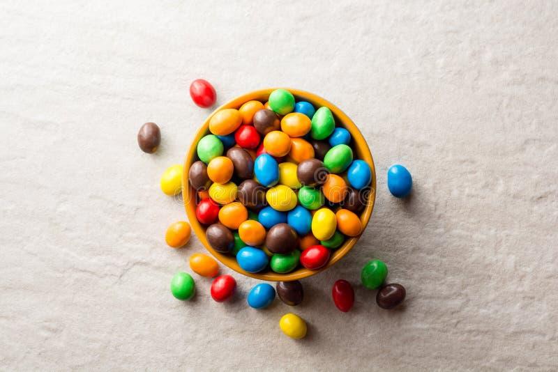 Kolorowi czekoladowi guziki w pucharze na szarość drylują tło obrazy royalty free