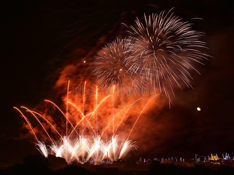 Kolorowi czerwoni fajerwerki w Zurrieq wiosce, Malta z domem zaświecają w tle, wybuchają, ciemny nieba tło i domu światło zdjęcie stock