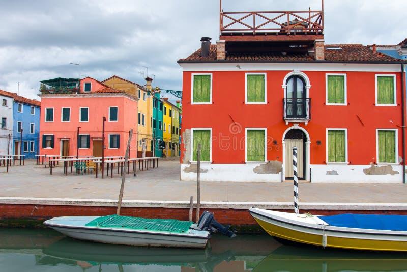 Kolorowi domy i ?odzie w wodnym kanale w Burano wyspie, Wenecja, W?ochy Burano pejza? miejski obraz royalty free