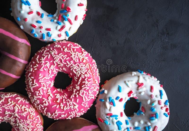 Kolorowi donuts na czerń kamienia stole Odgórny widok zdjęcia stock