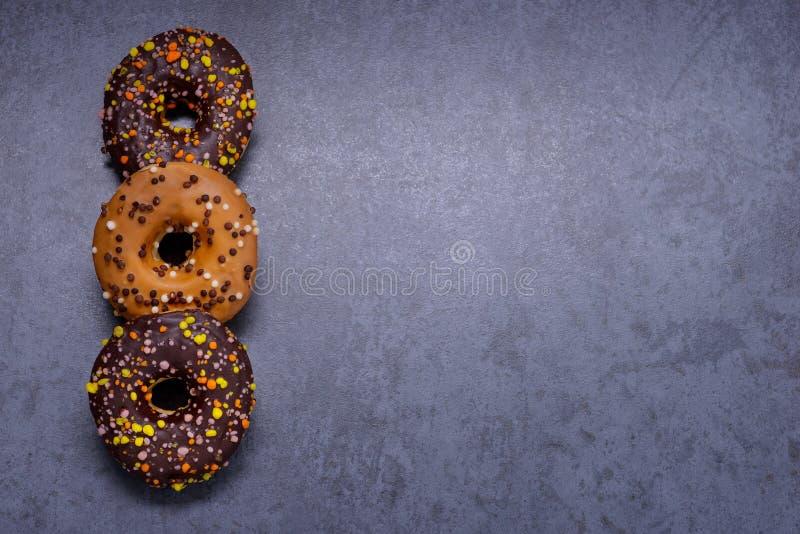 Kolorowi donuts z czekoladą na kamienia stole obraz royalty free
