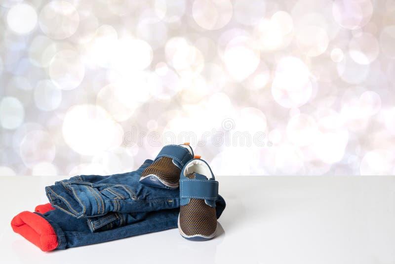 Kolorowi dziecko cajgi odziewaj? Modna czerwie? wyk?ada? thermojeans i modn? par? b??kitni sneakers na jaskrawym stole fotografia royalty free