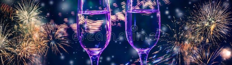 Kolorowi fajerwerki i dwa szkła fizz szampan z bąblami na w górę spada śnieżnego tła fotografia stock