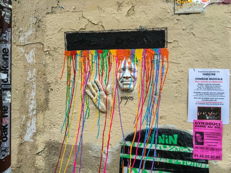 Kolorowi farba kapinosy leją się nad ścienną sztuki twarzą, ręką w Paryż i, Francja zdjęcia stock