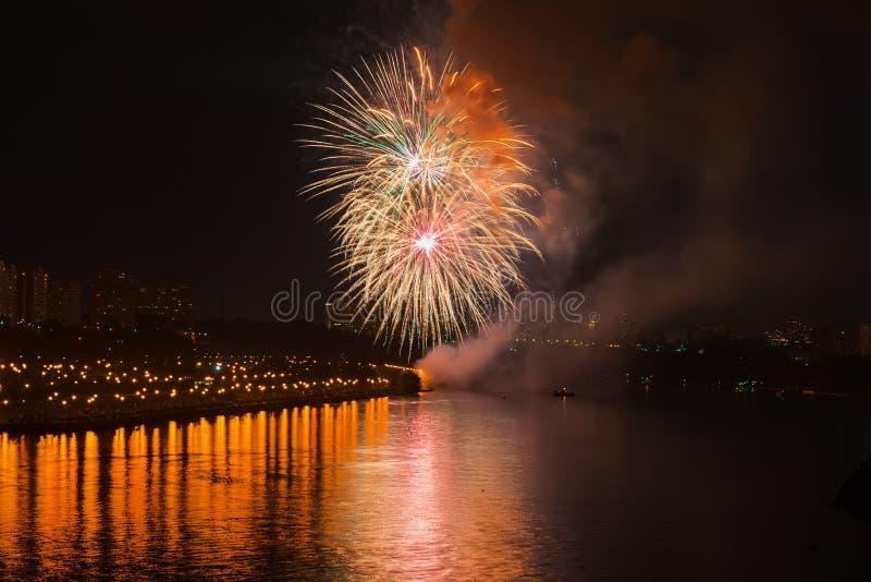 Kolorowi jaskrawi fajerwerki, salut złoci kolory w nocnym niebie z odbiciem w jeziorze Abstrakcjonistyczny wakacyjny tło zdjęcia stock