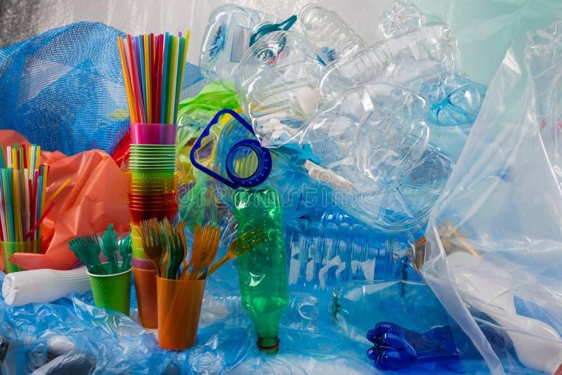 Kolorowi klingerytów rozwidlenia umieszczajÄ…cy w plastikowej filiżance i pozycji blisko wiÄ…zki Å›mieci zdjęcie stock