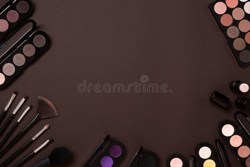 Kolorowi kosmetyki na brown miejscu pracy z kopii przestrzenią Kosmetyki uzupełniali artystów przedmioty: pomadka, oko cienie, pr obrazy royalty free