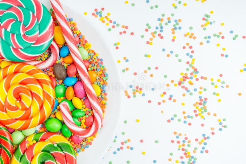 Kolorowi lizaki, confetti i różnorodni barwioni cukierki zamknięci w górę talerza na, obraz royalty free