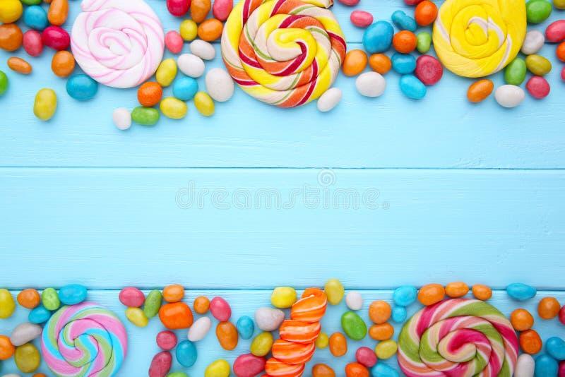 Kolorowi lizaki i różny barwiony round cukierek na błękitnym drewnianym tle zdjęcie stock