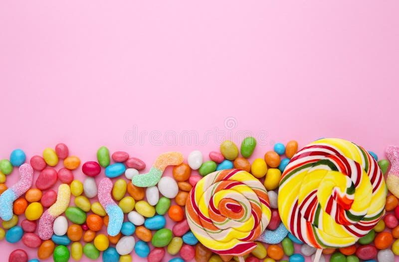 Kolorowi lizaki i r??ny barwiony round cukierek na r??owym tle obraz royalty free