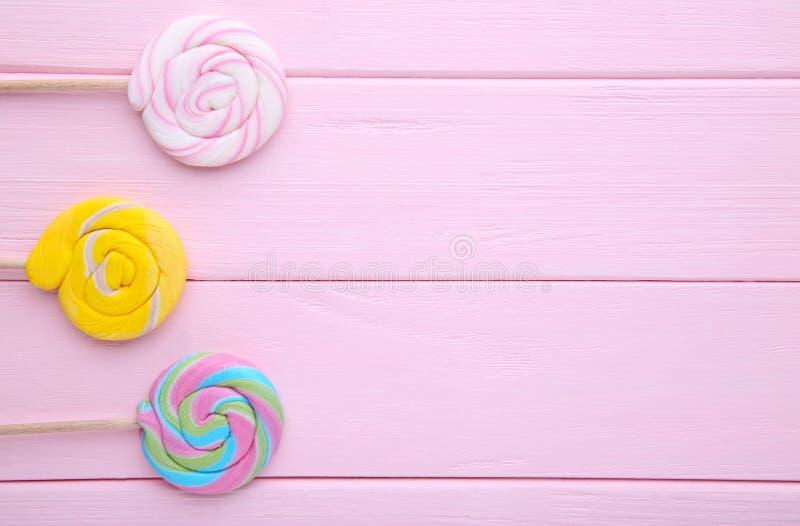 Kolorowi lizaki na różowym drewnianym tle, cukierki obraz stock
