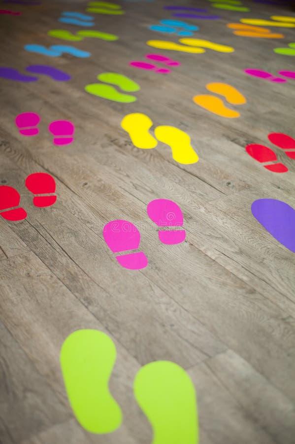 Kolorowi ludzcy odciski stopy na drewnianej podłoga fotografia stock