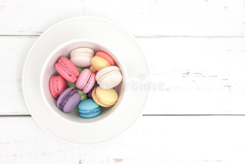 Kolorowi macarons w filiżance obraz stock