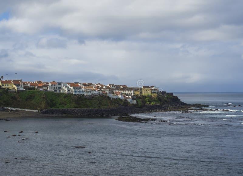 Kolorowi mali nabrzeżni wioska domy na skalistym lawowym brzeg nad Atlantyk ocean z wod morskich falami, cloouds i markotnym, zdjęcia royalty free