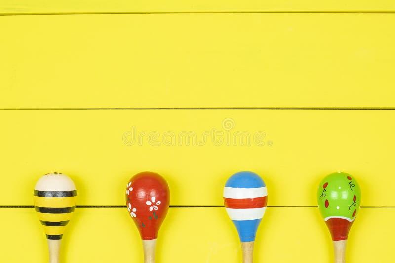 Kolorowi marakasy na żółtym drewnianych desek tle obraz stock