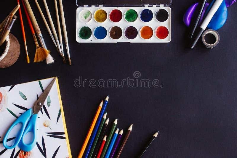 Kolorowi ołówek farb muśnięć nożyce i notatnik na chalkb zdjęcie stock