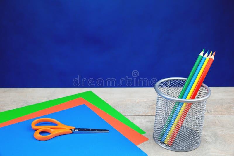 Kolorowi ołówki, materiały na drewnianym biurku obraz stock