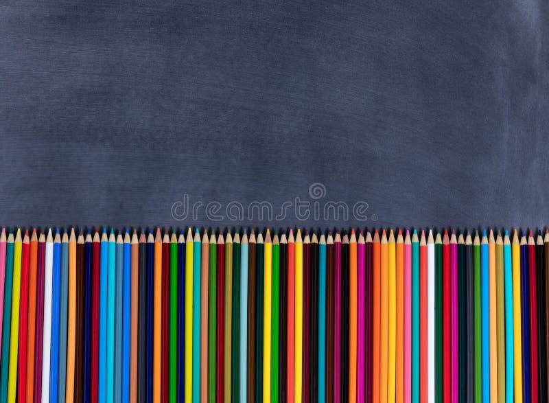 Kolorowi ołówki wykładali up na dnie wymazujący czarny chalkboard obrazy stock