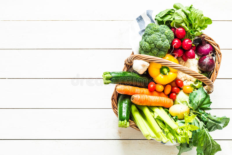 Kolorowi organicznie wiosen warzywa w łozinowym koszu na drewnie fotografia stock