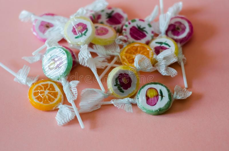 Kolorowi owocowi lizaki na różowym tle ale del, niezdrowy obrazy royalty free