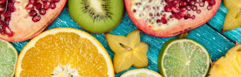 Kolorowi owocowi plasterki na błękitnej drewno powierzchni fotografia royalty free