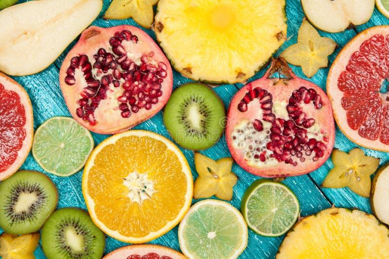 Kolorowi owocowi plasterki na błękitnej drewno powierzchni zdjęcie stock