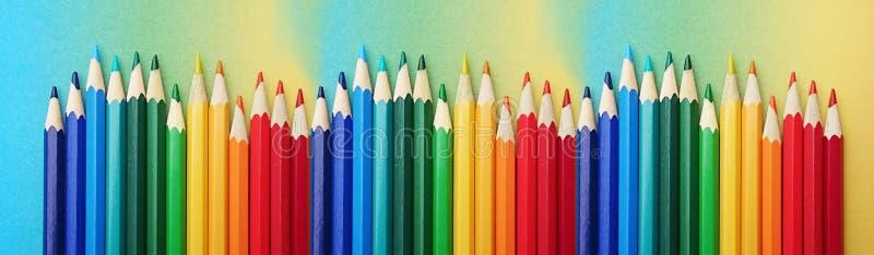 Kolorowi pióra układali w kolorach tęcza na kolorowym papierze w trakcie tęczy zdjęcie stock