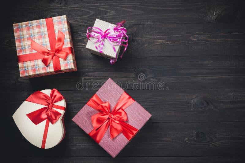 Kolorowi prezentów pudełka na ładnym ciemnym drewnianym tle Bożych Narodzeń lub valentines dnia tło z bezpłatną przestrzenią obrazy stock