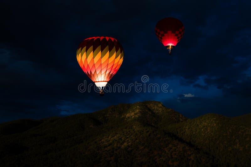 Kolorowi rozjarzeni gorące powietrze balony unosi się w nocnym niebie nad zalesionymi halnymi szczytami obraz royalty free