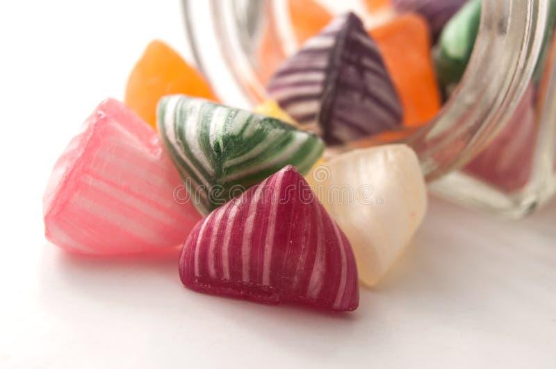 kolorowi tradycyjni cukierki spada od szklanego conta zdjęcie stock
