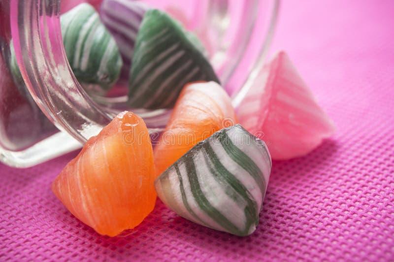 kolorowi tradycyjni cukierki spada od szklanego conta fotografia royalty free