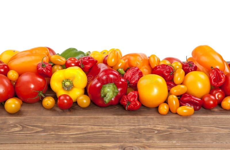 Kolorowi warzywa na białym drewnianym tle: pomidory i papryka obraz royalty free